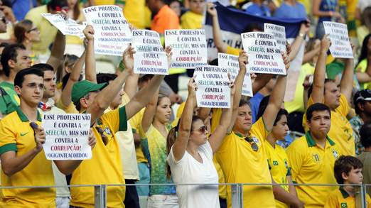 Protesters hold signs before the Confederations Cup Group A soccer match between Brazil and Mexico at the Estadio Castelao in Fortaleza