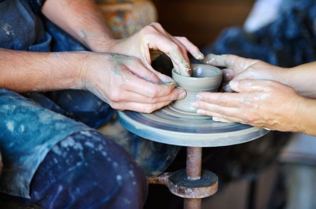 Two people at a potter's wheel