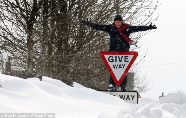 Give way for what?! Anna Ryder, clambers over a snowdrift that is as high as a road sign as winter continues in Sparrowpit, Derbyshire