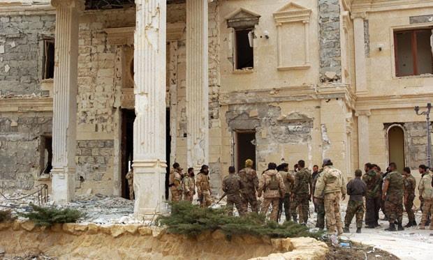 Tropas sírias são vistas na quinta-feira (24) ao lado de uma mansão pertencente à família real do Catar, na periferia da antiga cidade de Palmira (Foto: AFP)