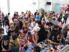 A crowd gathered at a vendor table looking at various anime items on sale