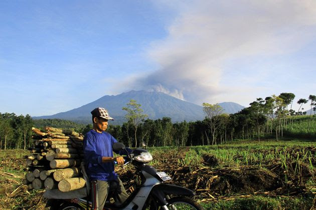 In this photograph taken on July 21, 2015, an Indonesian man carrying firewood on a motorcycle passes a field in Banyuwangi located in eastern Java island as Mount Raung volcano emits steam and ash.