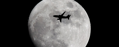 A plane flies across the moon (Dan Kitwood/Getty Images)