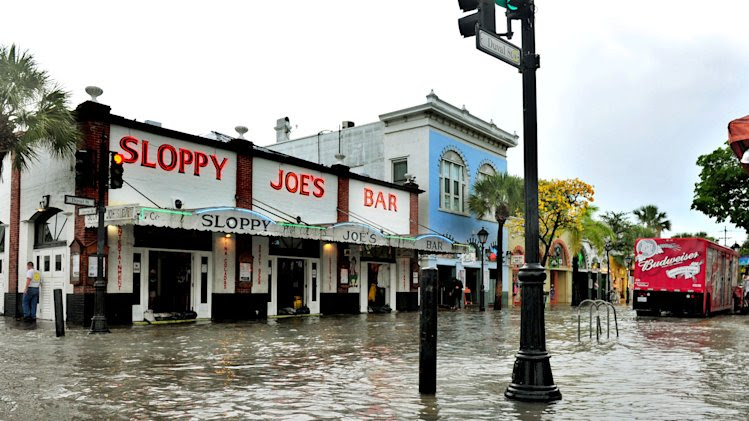 FILE - This Thursday, May 2, 2013 file photo shows flooding on Duval Street in Key West, Fla. after roughly five inches of rainfall. In many sea level projections for the coming century, the Keys, Miami and much of southern Florida partially sink beneath potential waves. (AP Photo/The Key West Citizen, Rob O'Neal)