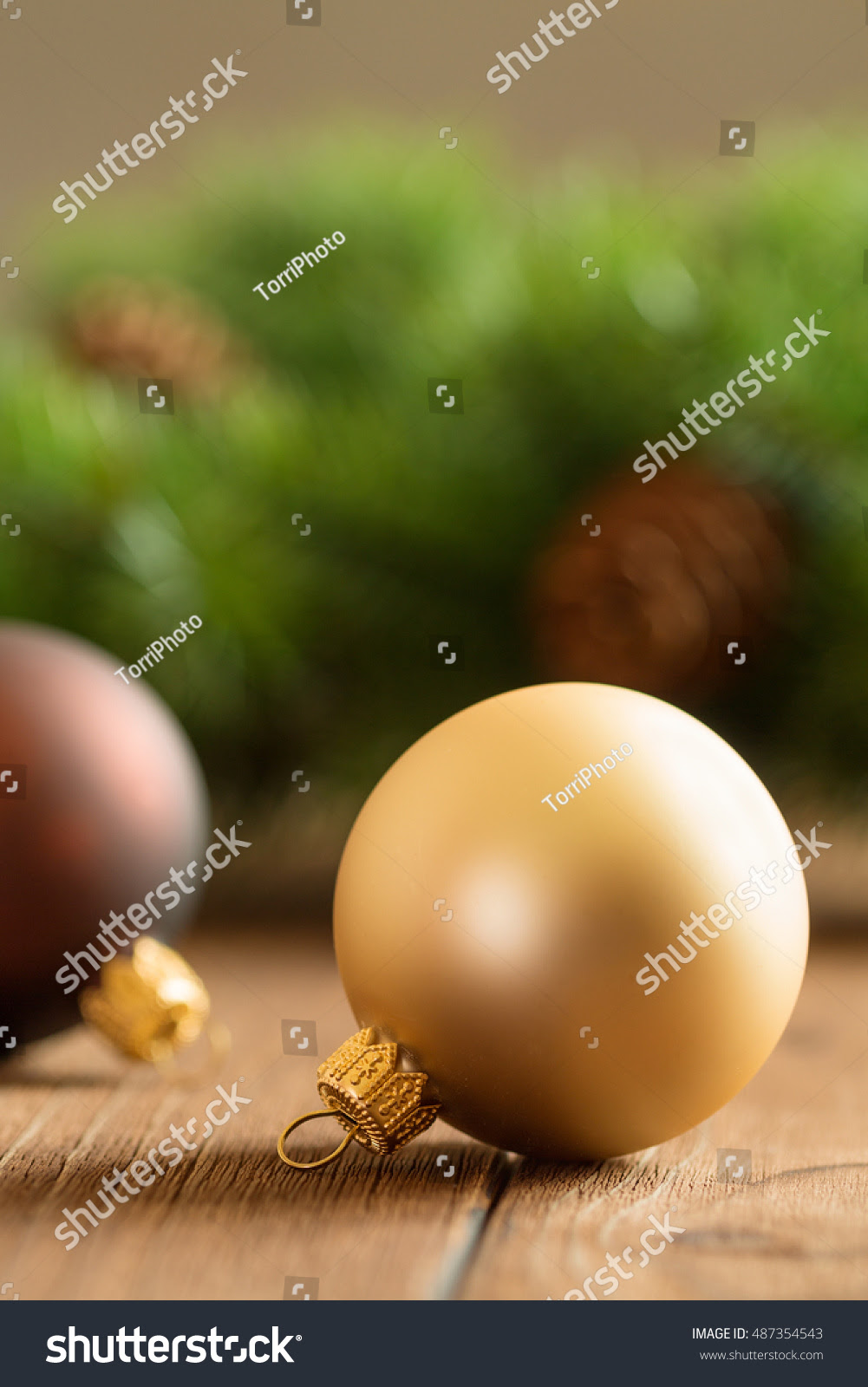 Christmas balls decorations on rustic wooden background with fir branch
