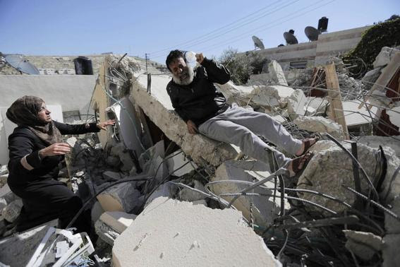 A Palestinian man reacts as he sits atop rubble after his home was demolished in Jabel Mukaber, a village in the suburbs of East Jerusalem, in this February 5, 2014 file picture. REUTERS-Ammar Awad-Files
