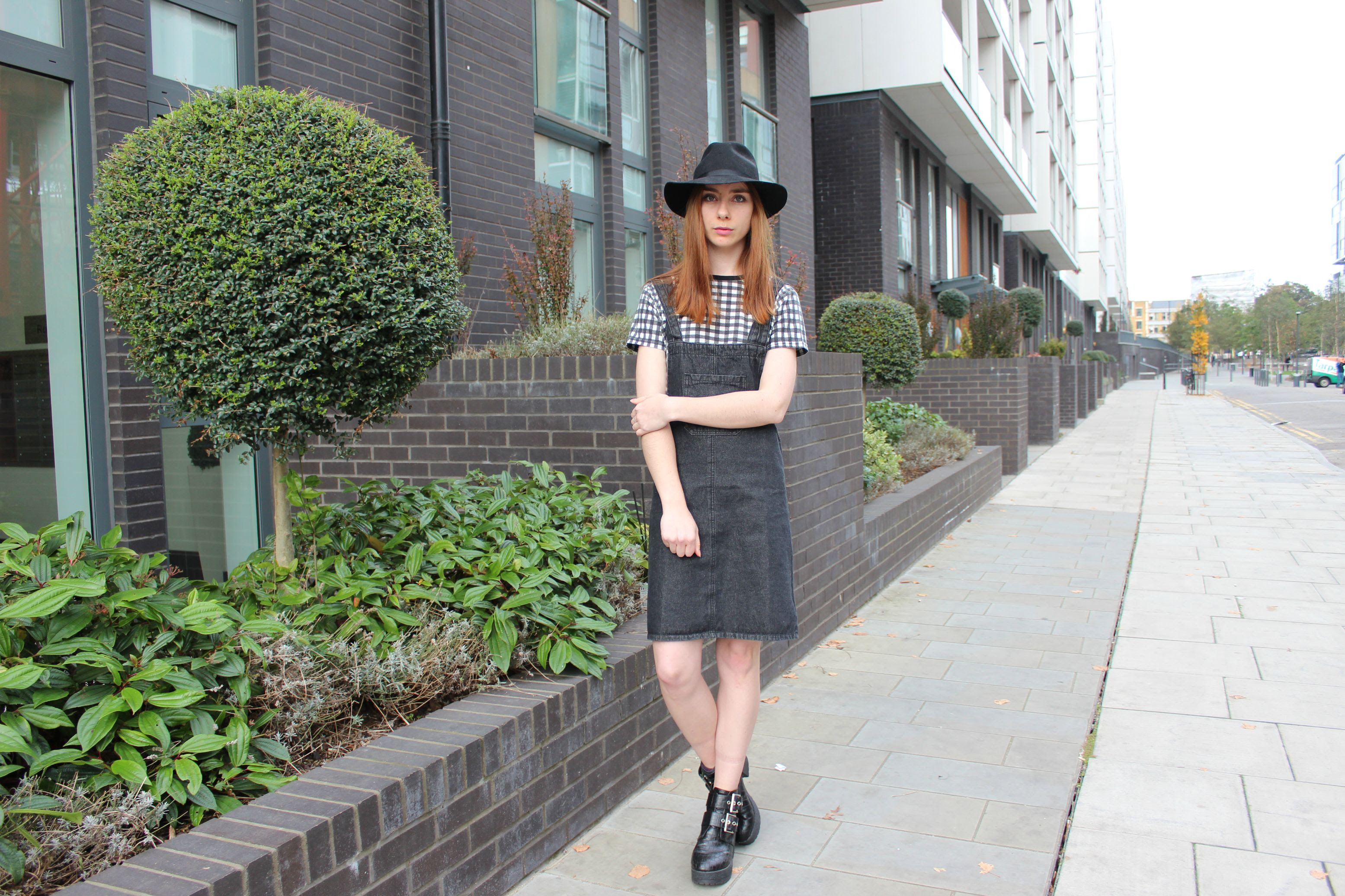 Denim pinafore dress, check tee and a fedora outfit