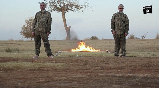 The two men are stood with their backs to the flames that will eventually kill them in a barbaric execution