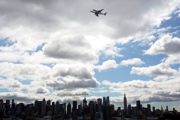 The shuttle Enterprise and NASA 905 fly over the New York City skyline on April 27, 2012.