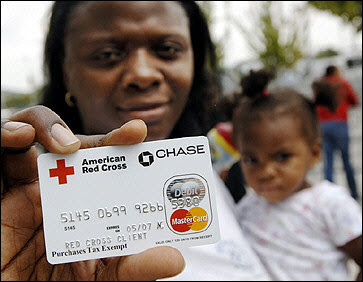 Hurricane Katrina evacuee Latesha Vinnett holds a debit card from the Red Cross with her daughter Mychal Boykins outside the Reliant Center in Houston, Texas.(AFP/Stan Honda)