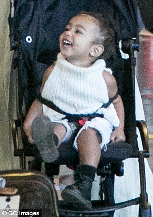 Giddy: The onlyonly child of Kim Kardashian and Kanye West giggled as she sat in her pram while her mother pushed them out of the Charles-de-Gaulle airport