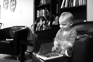 Toddler in chiar with book.