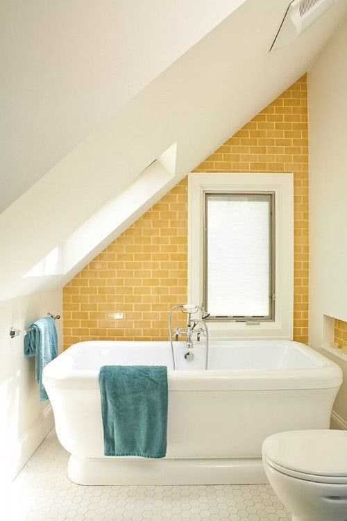 Love the angled ceiling, yellow subway tile and the pop of color with the towels. Renewal Design Build.