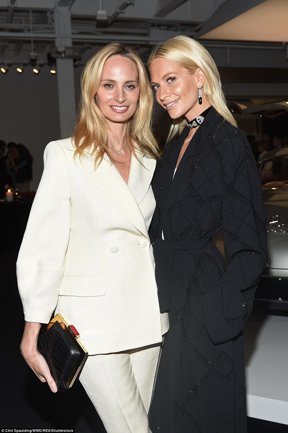 Top coat: Poppy Delevingne also attended - seen here with Lauren Santo Domingo (left) - wearing a silk black trenchcoat patterned with a sparkly diamond print by the designer