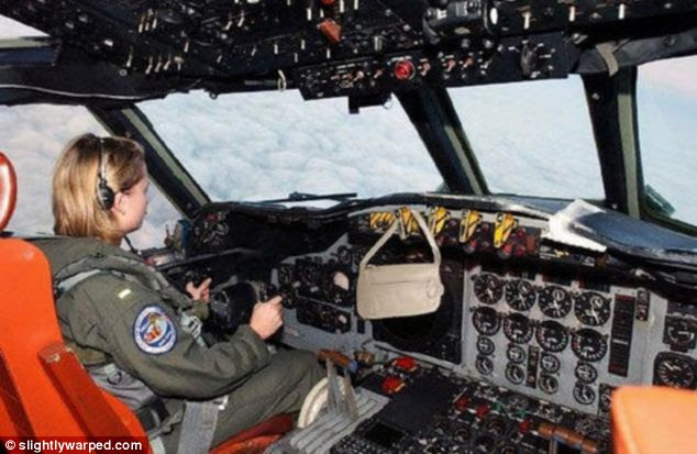 Woman behind the wheel: A female pilot hangs her handbag on the controls of this military aircraft