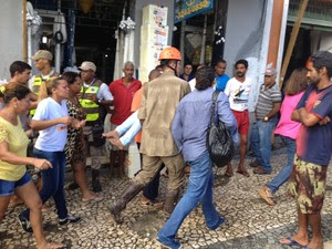 Filha da vítima sendo socorrida após deslizamento de terra em Salvador (Foto: Cássia Bandeira/G1)