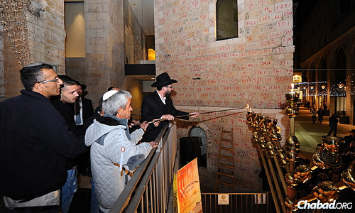 Kutner lights the first candle on the menorah, assisted by family members. (Photo: Mendy Hechtman)