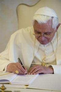 Pope Benedict XVI signs his encyclical 'Charity in Truth' at the Vatican July 6, 2009. REUTERS-Osservatore Romano