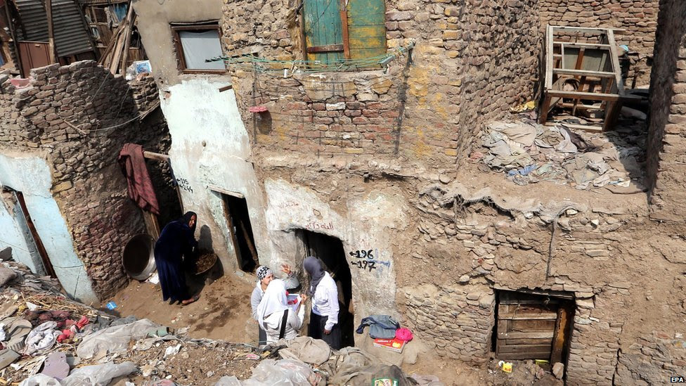 Egyptians stand in front of their houses at a slum in Ramlet Bulaq neighbourhood, Cairo, Egypt, 16 March 2015