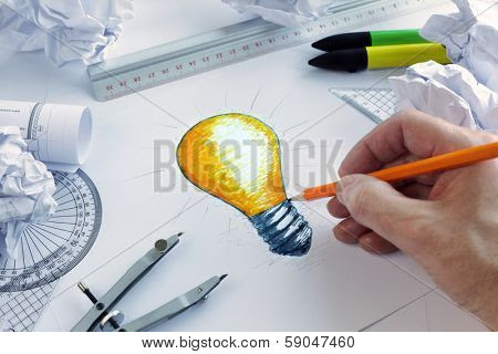 Picture or Photo of Designer drawing a light bulb, concept for brainstorming and inspiration