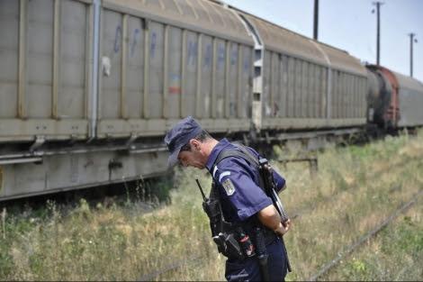 Un policía rumano frente al tren que transportaba armamento en Rumanía. | AP