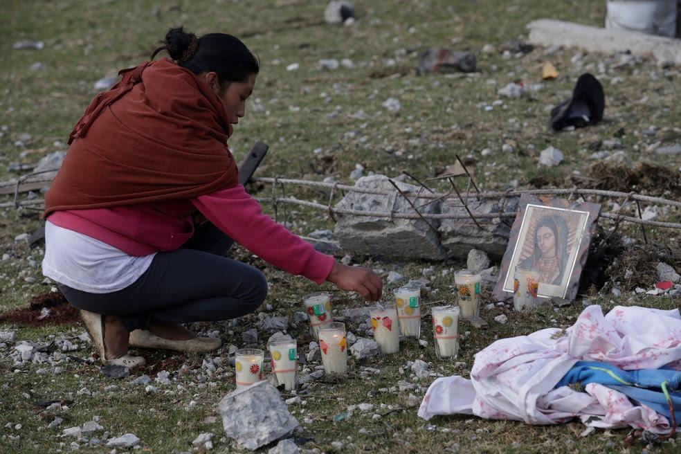 Moradora acende velas perto do lugar onde houve uma explosão de um depósito de fogos de artifício em San Isiro, Chilchotla, México  (Foto: Imelda Medina/Reuters)