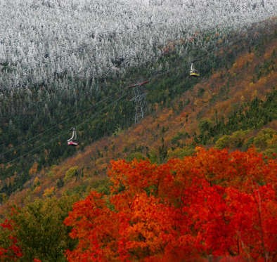 Tram cars take tourists up Cannon Mountain in Franconia , N.H., as snow meets with changing leaves Thursday, Oct. 1, 2009. (AP Photo/Jim Cole)