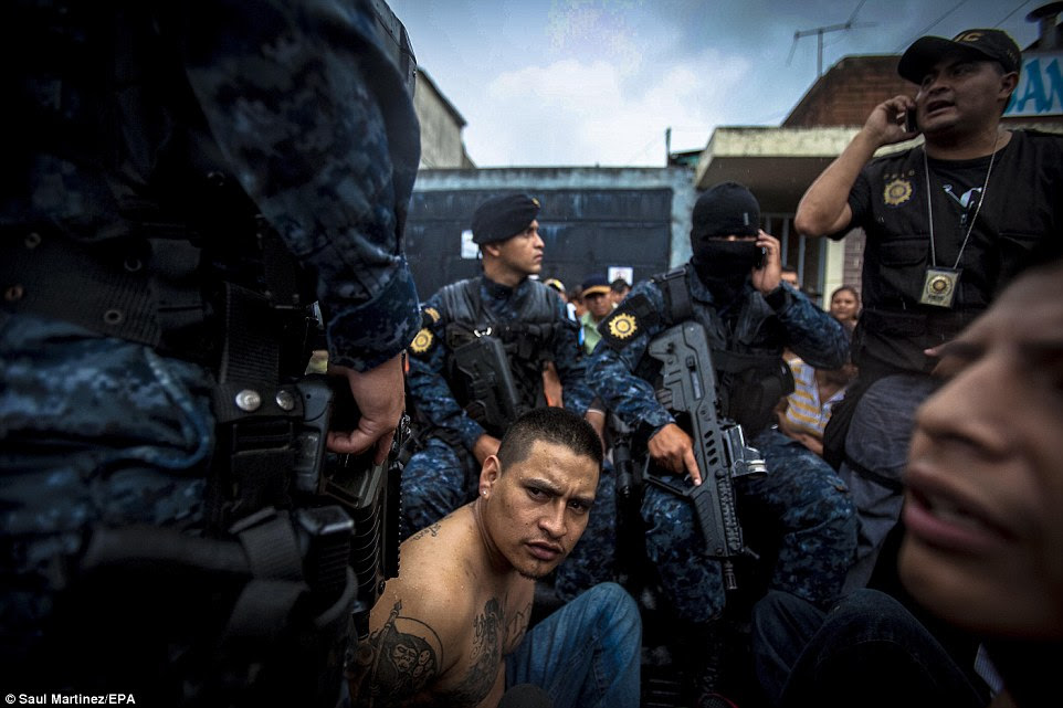 Captured:Guatemalan police officers, each carrying a gun and one wearing a balaclava, gather around William Lazaro, aka Scandalous, an alleged Mara-18 gang member. Certain neighbourhoods in Guatemala City are controlled by criminal gangs which have walled off their territories with concrete barriers