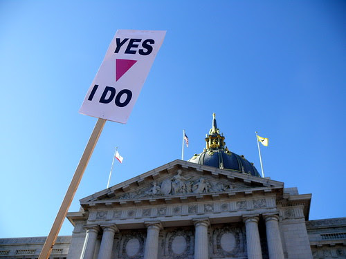 Photograph of San Francisco City Hall with sign that says Yes, I Do, with a pink triangle