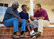 Photograph of three generations of men talking