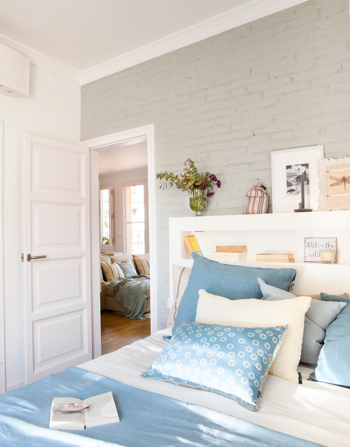 00429037. Dormitorio con pared de ladrillo en gris, ropa de cama en azul y blanco y cabecero con hueco de madera blanca 00429037