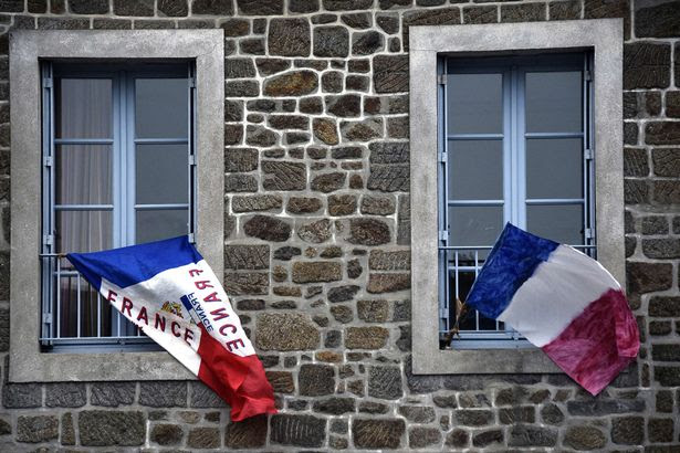 French national flags put on a window in Hede-Bazouges, north of Rennes, during the National Tribute to the 130 people killed in the November 13 Paris attacks