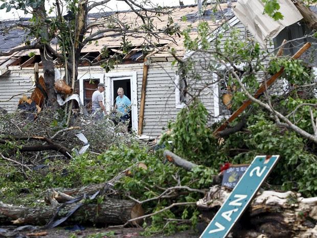 Um homem e uma mulher conversam na entrada de uma casa que foi destruída por tornado em Van, no Texas, na segunda-feira (11) (Foto: Reuters/Mike Stone)