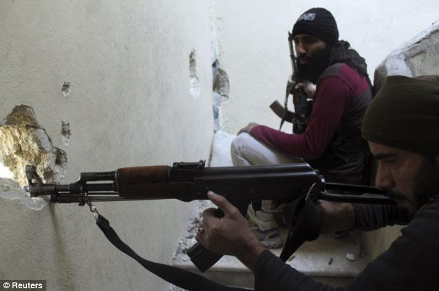 A Free Syrian Army fighter aims his weapon Salaheddine neighbourhood. Karan is said to have fought for the rebels alongside al-Qaeda