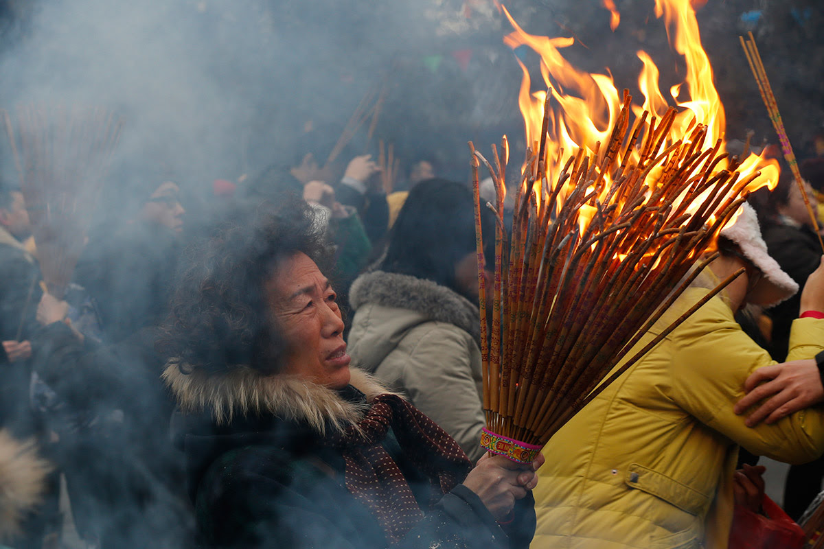 A woman burns incense as she pray for good fortune at Yonghegong Lama Temple in Beijing