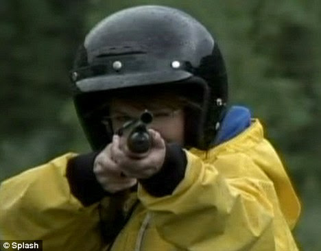 Staring down the barrel: Mrs Palin aims a gun in the direction of a camera in another scene from her show