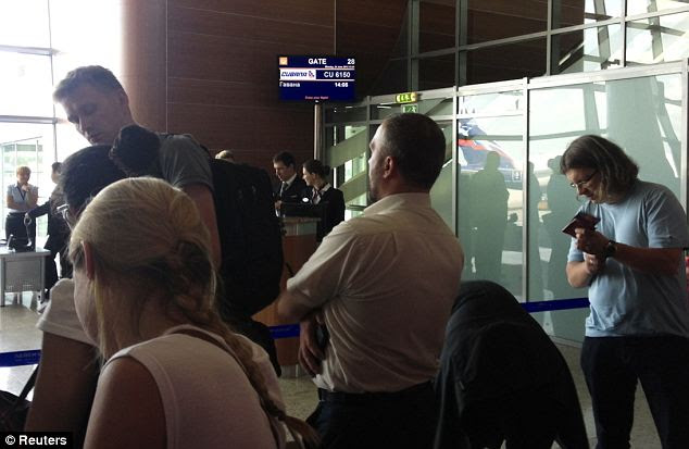 Where is he? Passengers queue to board a plane to Cuba at a terminal of Moscow's Sheremetyevo airport. But Snowden was nowhere to be seen