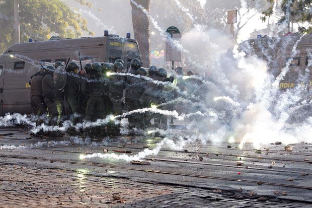 Policiais se protegem de artefato atirado por manifestantes (Foto: AP)