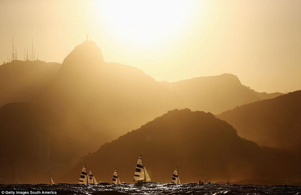 470 velejadores da classe dos homens retornar à costa, sob um sol de ajuste após uma corrida, sob a estátua do Cristo Redentor