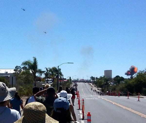 People head towards the main airfield at Marine Corps Air Station (MCAS) Miramar as two AH-1 Cobra attack helicopters approach an explosion in the distance...on September 24, 2016.