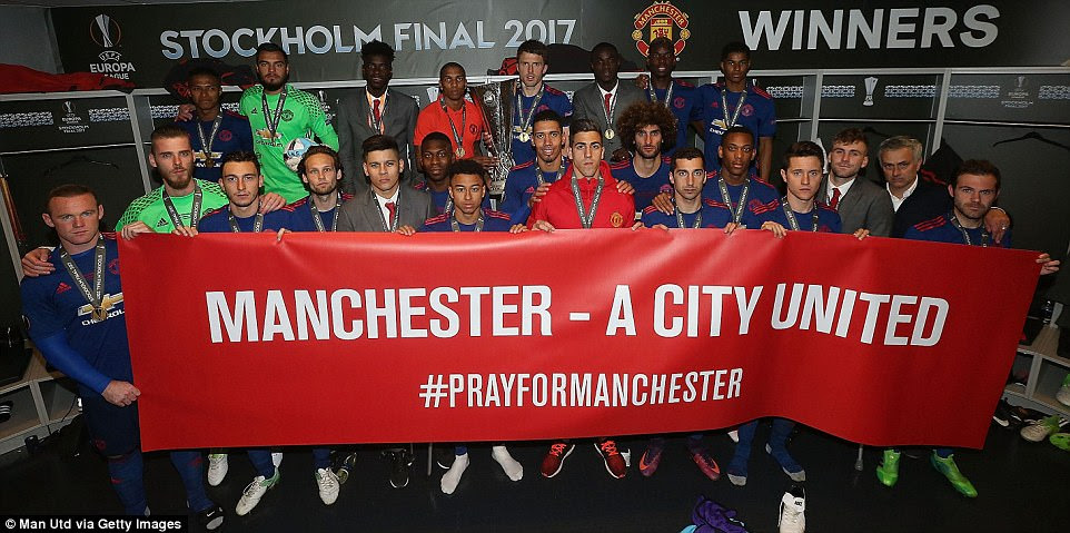 The match-winning United stars pose with a banner as they pay their respects to the victims of this week's Manchester attack