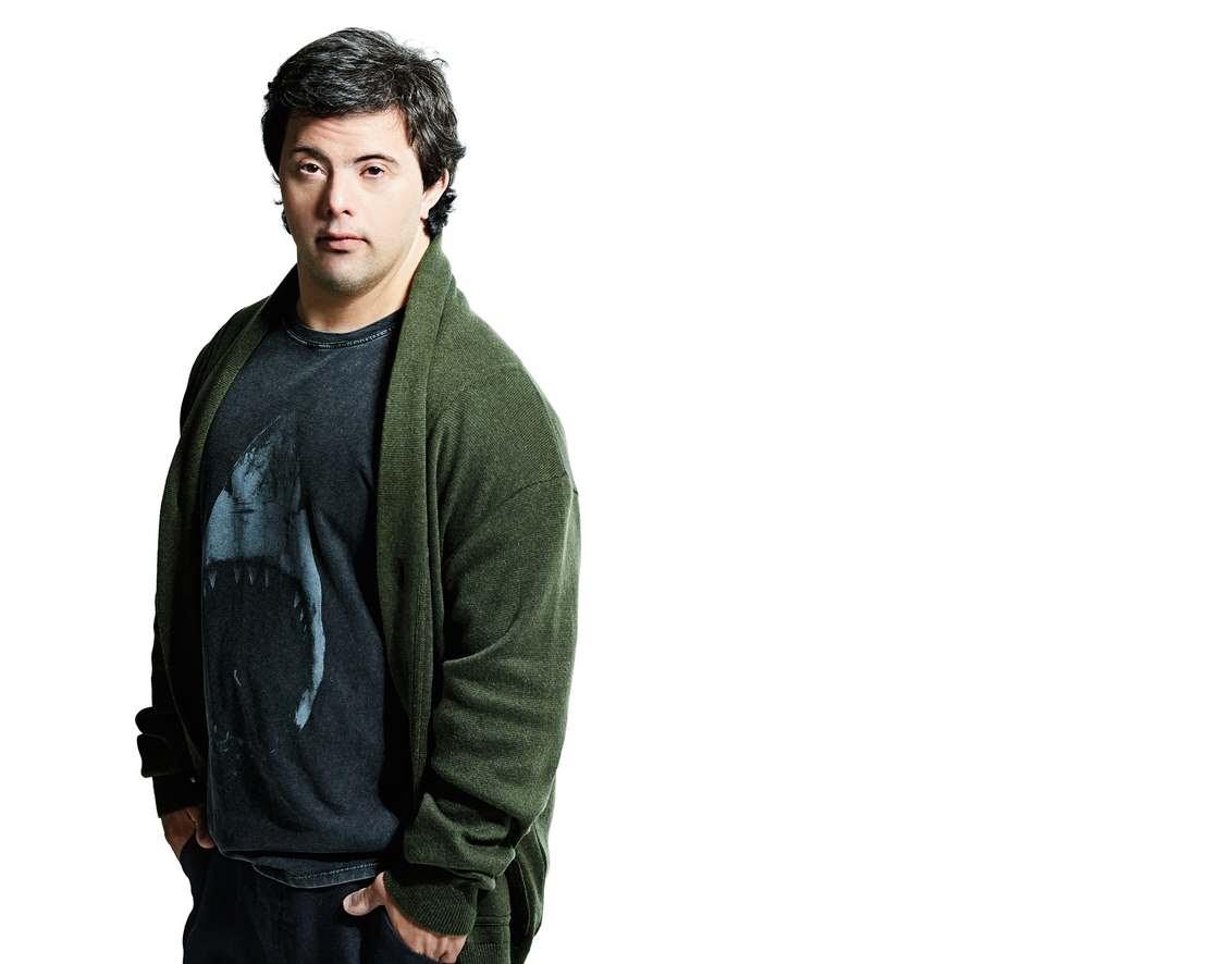 Modelo com sindrome de down veste camiseta preta com um tubarao e casaco verde.