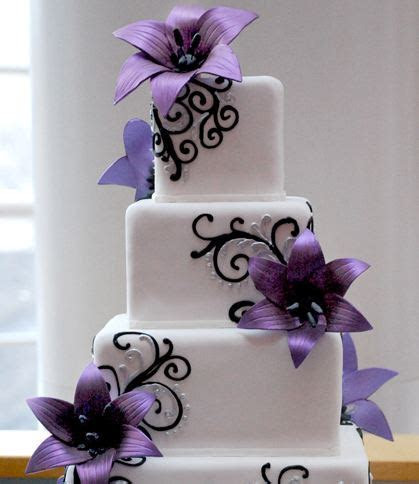 Four tier white cubic wedding cake with purple flower