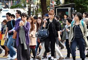 Pedestrians use their smartphones on a street in Tokyo, …