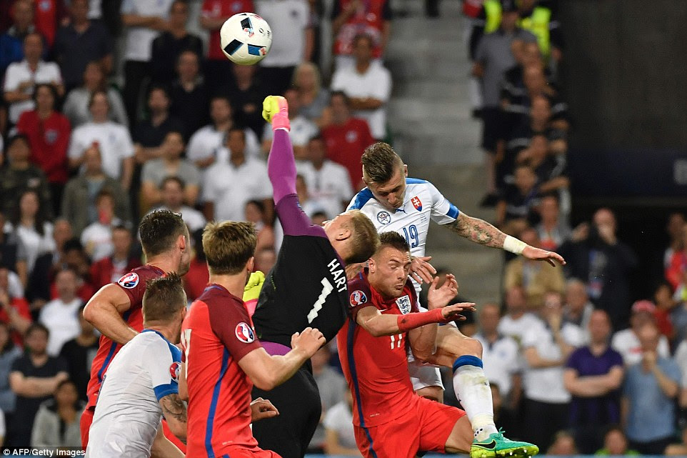 Hart gets himself in between a clutch of bodies to punch the ball clear on a rare Slovakian attack during the Group B match