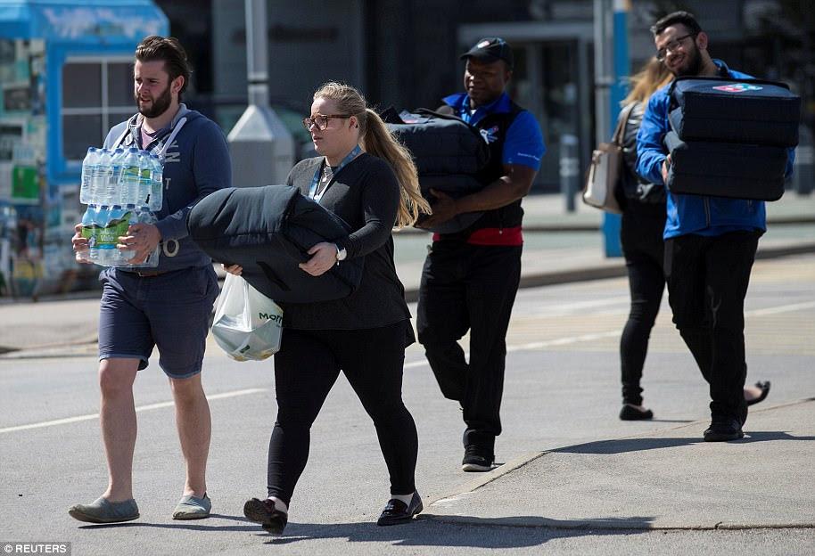 Voluntários como Dominos Os motoristas de entrega de pizza trazem suprimentos para o estádio Etihad, onde as famílias das vítimas estão sendo confortadas