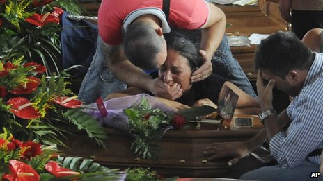People mourn their loved ones amongst the coffins of some of the victims of Sunday's bus crash prior to the start of their funeral service, in Pozzuoli, near Naples, southern Italy, Tuesday, July 30, 2013.