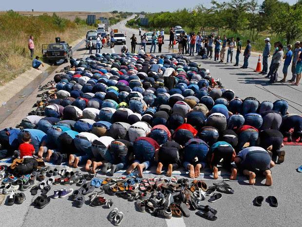 Refugiados fazem oração em rodovia perto da cidade de Edirne, na Turquia, nesta sexta (18) (Foto: Osman Orsal/Reuters)