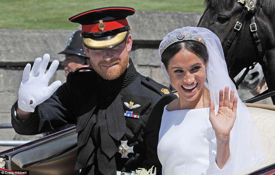Meghan y Harry saludan a los fanáticos reales durante su procesión abierta a través de Windsor después de la ceremonia de la boda