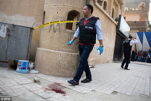 A pool of blood could be seen on the ground as a security official inspected the damage at Mar Mina church following an attack in the district of Helwan, southeastern Cairo